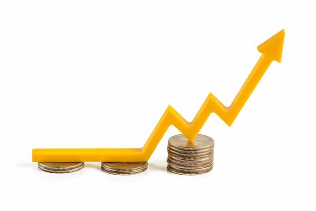 Ceny podwyżek inflacji. izolat wzrostu rynku finansowego na białym tle. żółta strzałka na wykresie wskazuje w górę. zbuduj wykres na stosach monet