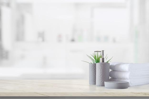 Ceramiczna butelka szamponu z białymi bawełnianymi ręcznikami na marmurowym blacie nad łazienką
