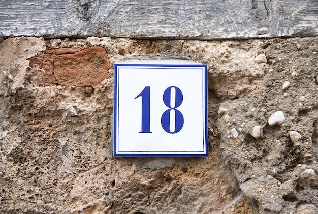 Ceramiczna cyfra osiemnaście na szarej kamiennej ścianie