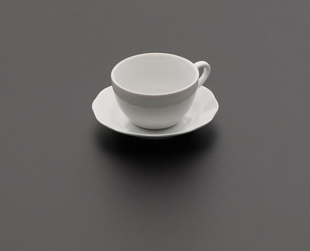 Ceramiczna filiżanka do herbaty i spodek na czarnym tle