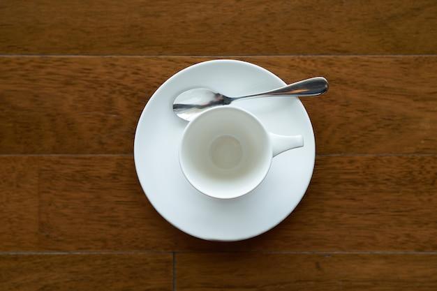 Ceramiczna filiżanka herbaty lub kawy z łyżeczką i talerzem na drewnianej palecie