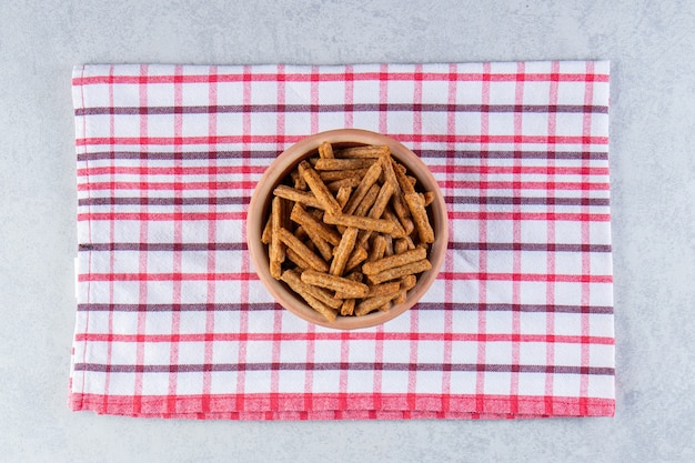 Ceramiczna miska smaczne chrupiące krakersy na tle kamienia.
