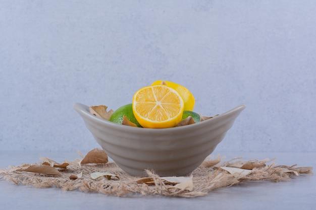 Ceramiczna miska świeżych soczystych cytryn na kamieniu.