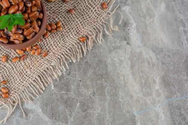 Ceramiczna miska z gotowanej fasoli z płótnem na marmurowej powierzchni.