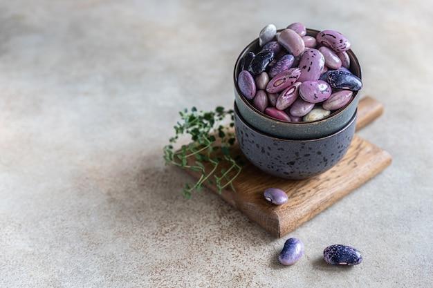 Ceramiczna miska z kolorowymi roślinami strączkowymi i tymiankiem, betonowe tło. wegański produkt wysokobiałkowy.