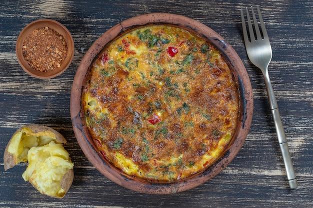 Ceramiczna miska z warzywną frittatą, proste wegetariańskie jedzenie. frittata z pomidorem, papryką, cebulą i serem na drewnianym stole, z bliska. włoski omlet jajeczny, widok z góry