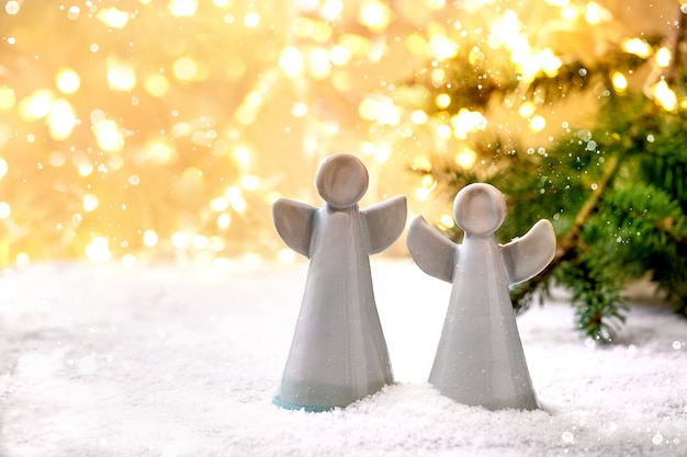 Ceramiczne anioły świąteczne. zestaw dwóch ręcznie robionych świątecznych dekoracji aniołów na śniegu z bokeh świątecznymi światłami i gałęziami jodły.
