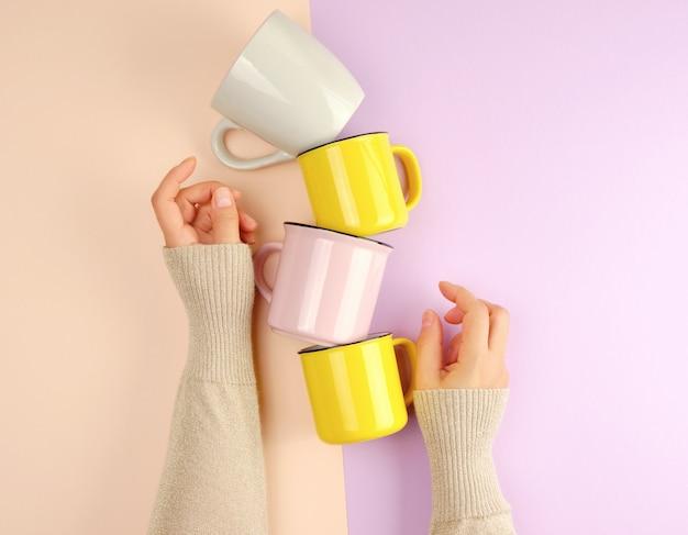 Ceramiczne kubki na stos są podtrzymywane przez kobiecą rękę