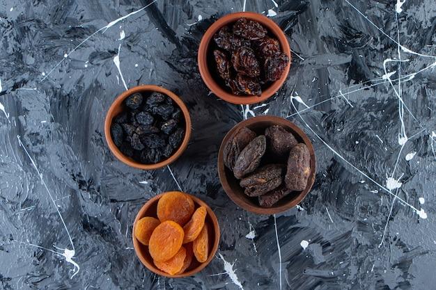 Ceramiczne miski smacznych suszonych owoców na marmurowej powierzchni.