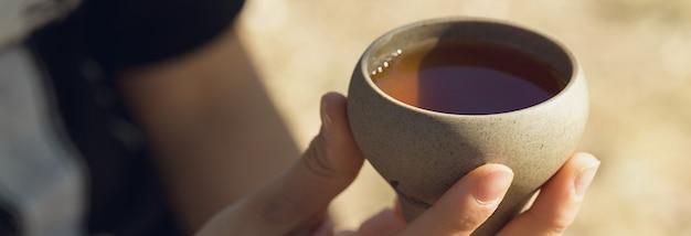 Ceramiczne miski wykonane z gliny na drewnianym tle. dziewczyna pije chińską herbatę.