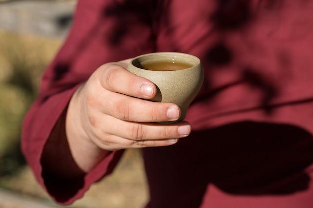 Ceramiczne miski wykonane z gliny na drewnianym tle. mężczyzna pije chińską herbatę.