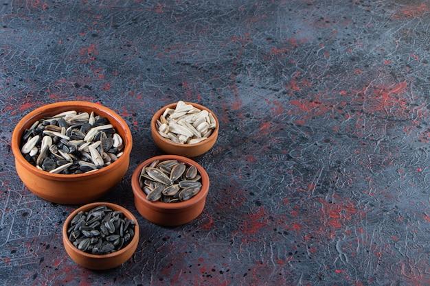 Ceramiczne miski z chrupiącymi nasionami słonecznika na ciemnej powierzchni.