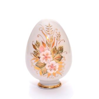 Ceramiczne porcelanowe ozdobne jajko z malowanymi kwiatami na stojaku na prezenty wielkanocne, na białym tle odizolowane