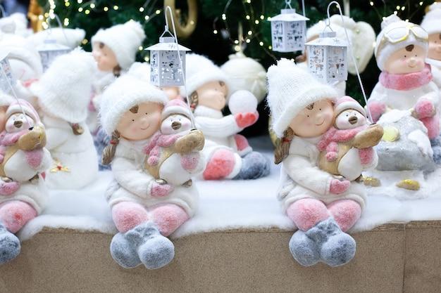 Ceramiczne świąteczne statuetki dziewcząt w strojach zimowych z pingwinem i latarnią. figurki świąteczne dzieci - dziewcząt i chłopców w zimowych ubraniach: czapka, futro, buty. dekoracje na boże narodzenie. nowy rok