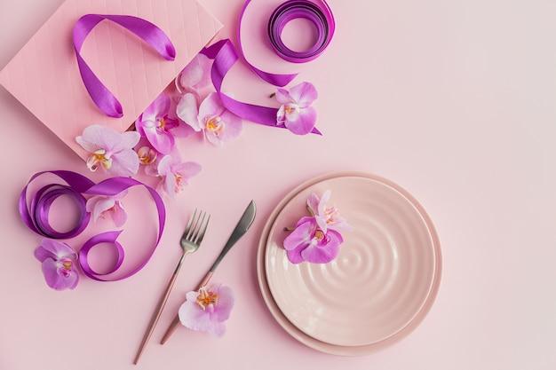 Ceramiczne talerze, sztućce, torebka prezentowa z fioletowymi wstążkami i różowymi kwiatami orchidei