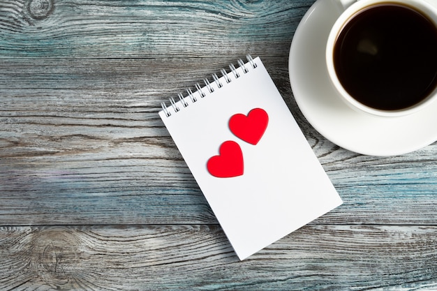 Ceramiczny biały kubek do kawy i dwa czerwone serca na notatniku.