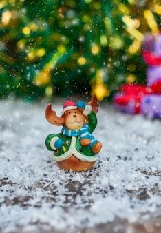 Ceramiczny bożenarodzeniowy zabawkarski łoś w świątecznych ubraniach stoi w śniegu