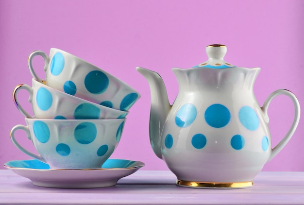 Ceramiczny czajniczek, stos filiżanek w kropki