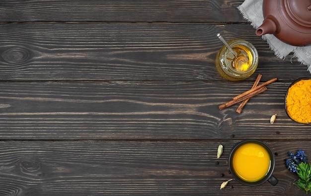 Ceramiczny imbryk z herbatą i miseczka z mieloną kurkumą i składnikami do przygotowania herbaty