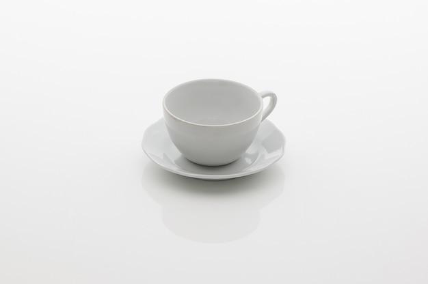 Ceramiczny kubek kuchenny na herbatę i spodek na białym tle