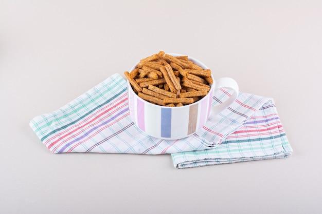 Ceramiczny kubek smacznych chrupiących krakersów na marmurowym tle. zdjęcie wysokiej jakości