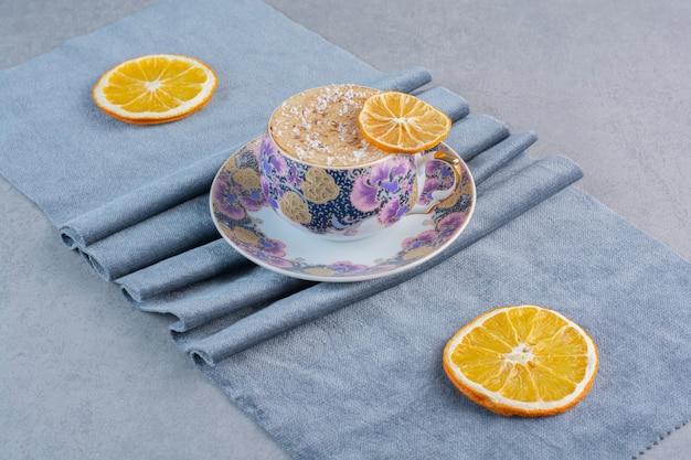 Ceramiczny kubek spienionej gorącej kawy umieszczony na niebieskim materiale.