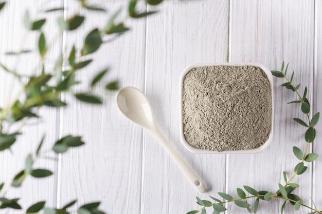 Ceramiczny puchar z zielonym glina proszkiem i świeżymi eukaliptusowymi liśćmi na białym tle. koncepcja pielęgnacji twarzy i ciała.