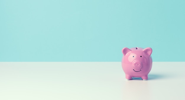 Ceramiczny różowy skarbonka na niebieskim tle. koncepcja zwiększania dochodów z rachunków bankowych, oszczędności, miejsca kopiowania