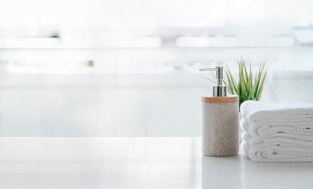 Ceramiczny szampon, butelka mydła i ręczniki na blacie nad pokojem kuchennym. biały górny stół i miejsce.