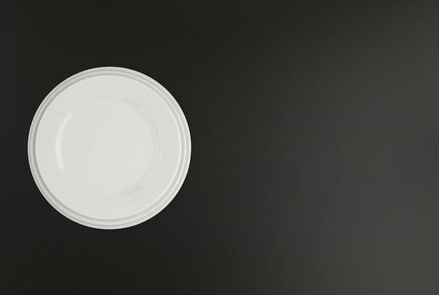 Ceramiczny talerz kuchenny na czarnym tle, widok z góry