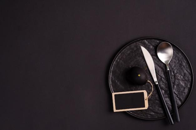 Ceramiczny talerz, łyżka i nóż z pomalowanym czarnym jajkiem wielkanocnym i tablica tekstu na tym samym kolorze tła.