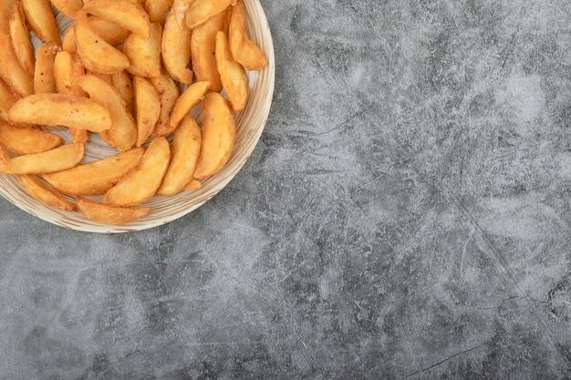 Ceramiczny talerz smacznych kawałków smażonych ziemniaków na kamiennym tle.