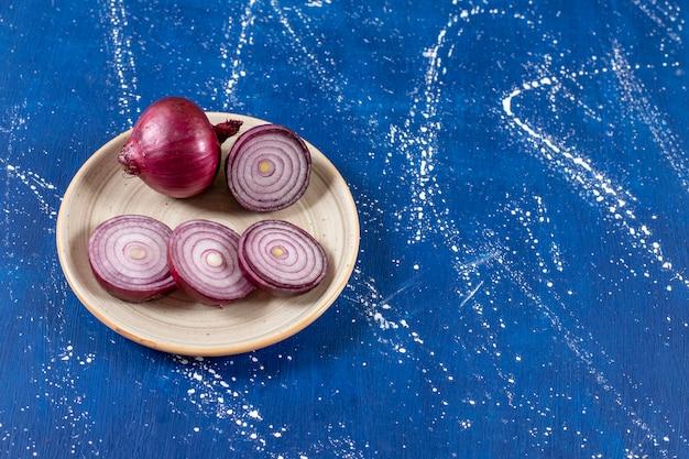 Ceramiczny talerz z fioletowymi krążkami cebuli na marmurowej powierzchni