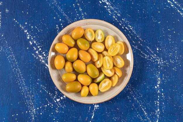 Ceramiczny talerz z pokrojonymi świeżymi owocami kumkwatu na marmurowej powierzchni.