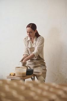 Ceramika w toku. kobieta stojąca przy kole garncarskim i wyglądająca na zaangażowaną