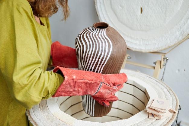 Ceramistka po wypaleniu wyjmuje z pieca. mistrz ceramik pracujący w pracowni garncarskiej. proces tworzenia ceramiki.