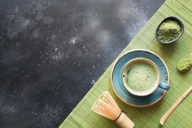 Ceremonia organiczna zielona herbata matcha na czarnym stole. widok z góry. miejsce na tekst.