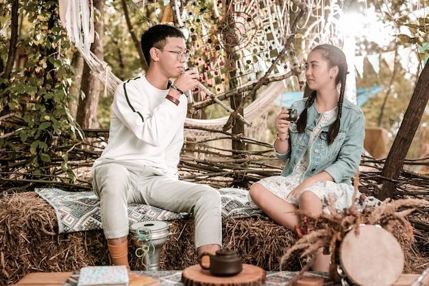 Ceremonia poranna. zachwycona długowłosa dziewczyna siedzi obok swojego partnera i rozkoszuje się ceremonią parzenia herbaty