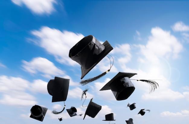 Ceremonia rozdania dyplomów, czapki rozdania dyplomów, czapka rzucona w powietrze z błękitnym streszczeniem.