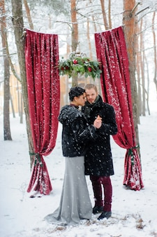 Ceremonia ślubna dla dwojga w pobliżu czerwonego łuku
