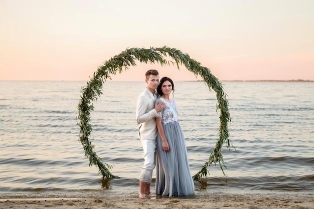 Ceremonia ślubna poza obiektem na plaży o zachodzie słońca. państwo młodzi stoją w pobliżu ołtarza weselnego