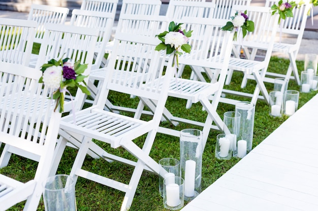 Ceremonia ślubna w ogrodzie. białe drewniane krzesła ozdobione kwiatami i świecami stojących w rzędach.