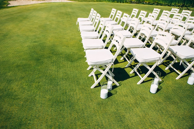 Ceremonia ślubna w przyrodzie. rzędy białych krzeseł na trawniku.
