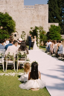 Ceremonia ślubna z wieloma gośćmi siedzącymi na krzesłach na trawniku