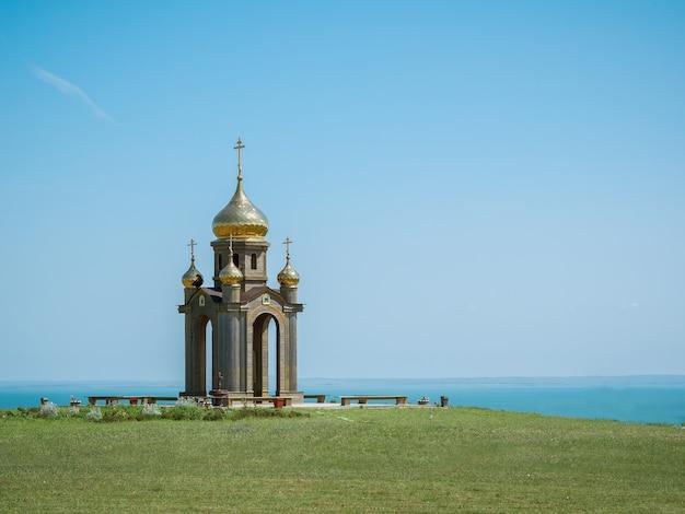 Cerkiew ze złotymi kopułami nad brzegiem morza.
