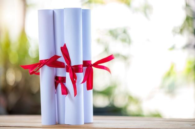 Certyfikat absolwenci zawiązali czerwoną wstążkę na drewnianej podłodze.