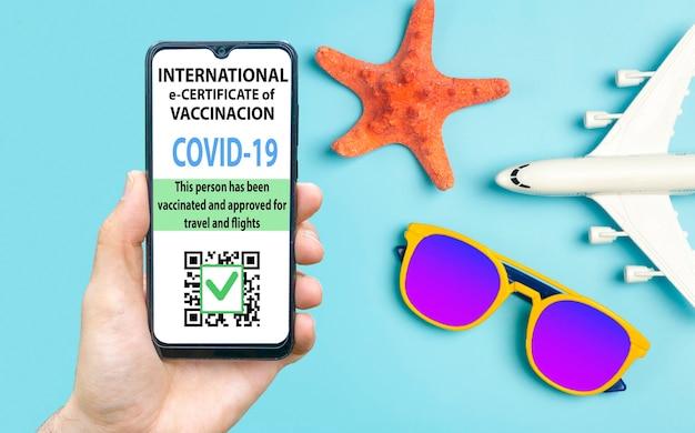 Certyfikat szczepień koronawirusowych lub paszport szczepionki dla koncepcji podróżnych. e-paszport odporny na covid-19 w aplikacji mobilnej na smartfony do podróży międzynarodowych. niebieskie tło z okularami przeciwsłonecznymi,