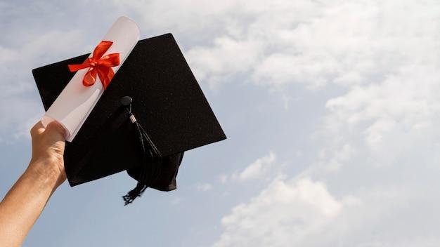 Certyfikat z wstążką i kokardą i kapeluszem ukończenia szkoły