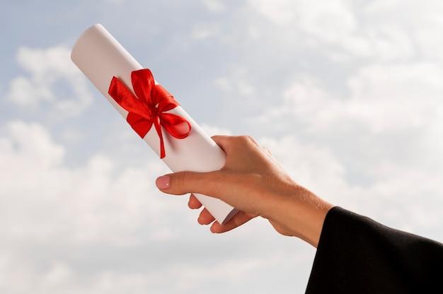 Certyfikat ze wstążką i kokardką trzymaną w dłoni