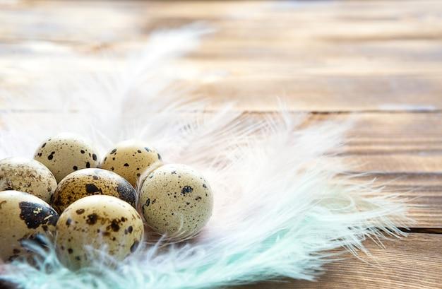 Cętkowane jaja przepiórcze na drewnianym stole w gnieździe z delikatnych, pastelowych piór.